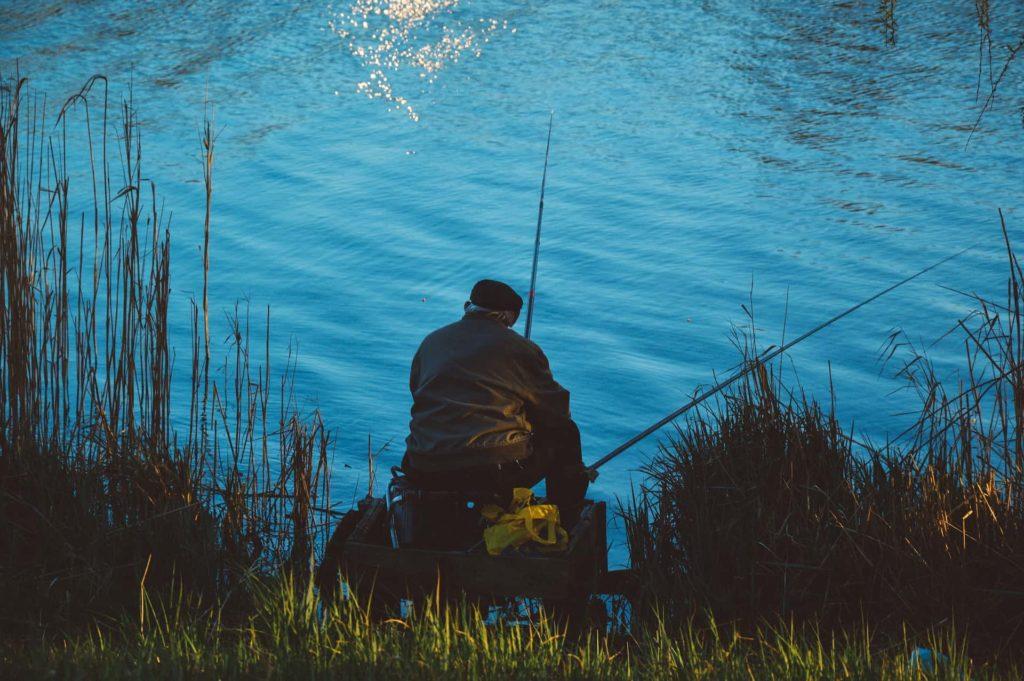 Angler sitzt am Ufer